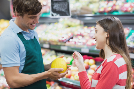 shop assistant: Shop assistant giving advises to a customer in a grocery shop