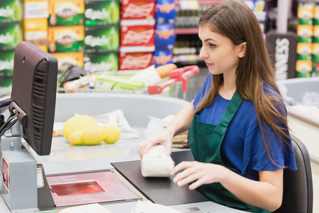 beeping: Woman cashier beeping an item on a grocery Stock Photo