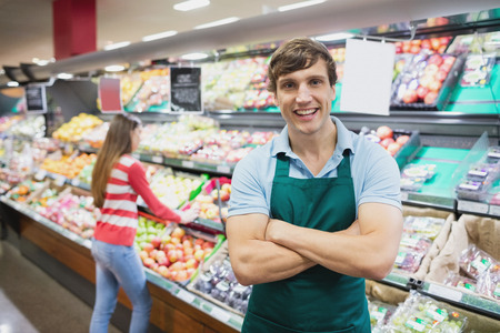 Assistente di negozio che propone con le braccia incrociate in un negozio di alimentari