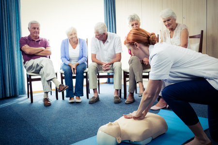 sheltered accommodation: Nurse teaching first aid to a group of seniors in the retirement house Stock Photo