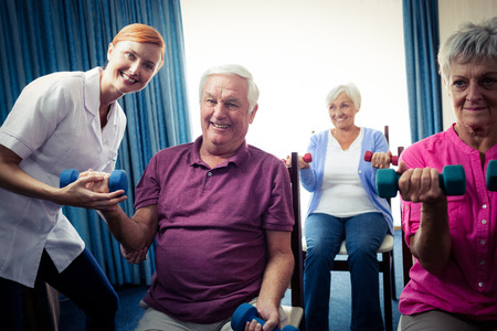 sheltered accommodation: Group of seniors doing exercises with nurse in the retirement house Stock Photo