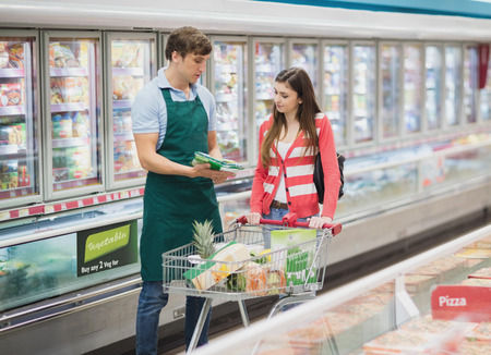 grocer: A man grocer advising his customer on a grocery Stock Photo