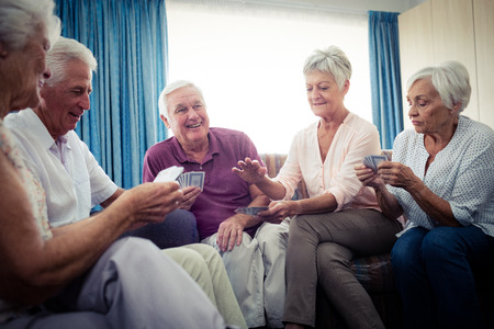sheltered accommodation: Group of seniors playing cards in the retirement house Stock Photo