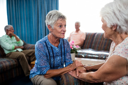 sheltered accommodation: 2 senior women interacting in the retirement house