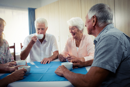 sheltered accommodation: Group of seniors drinking coffee in the retirement house