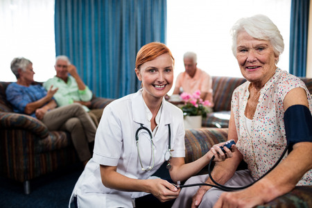 pensioner: Nurse taking care of pensioner in the retirement house