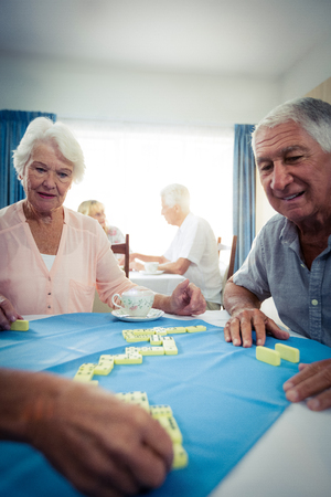 sheltered accommodation: Group of seniors playing dominoes in the retirement house