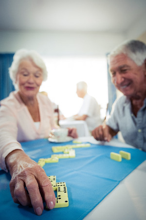 Group of seniors playing dominoes in the retirement house