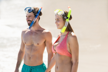 diving mask: Happy young couple wearing diving mask standing on beach Stock Photo