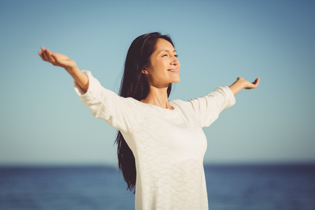 escapism: Happy woman standing with arms outstretched on beach
