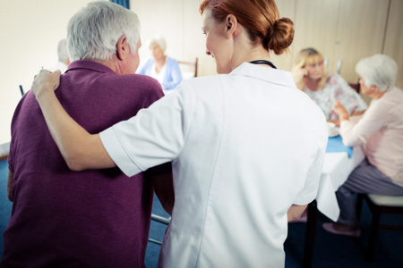 sheltered accommodation: Nurse assisting a senior using a walker in the retirement house