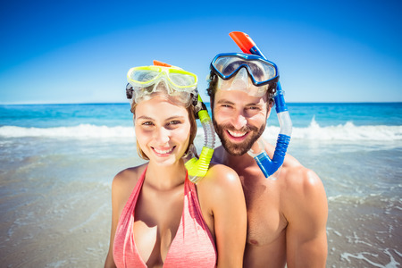 diving mask: Portrait of happy young couple wearing diving mask on beach