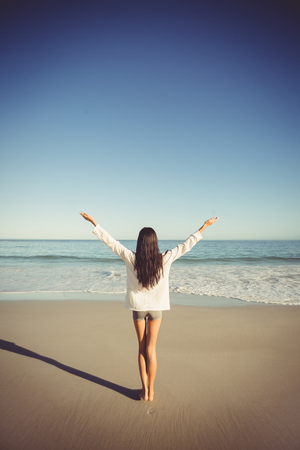 escapism: Rear view of woman standing with arms outstretched on beach Stock Photo