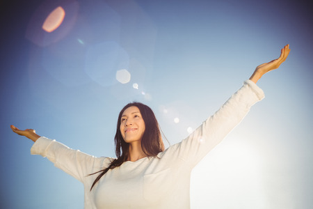 outstretched: Happy woman standing with arms outstretched on beach