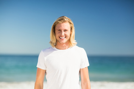 escapism: Portrait of young man smiling on beach