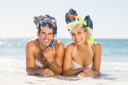 diving mask: Portrait of happy young couple wearing diving mask lying on beach