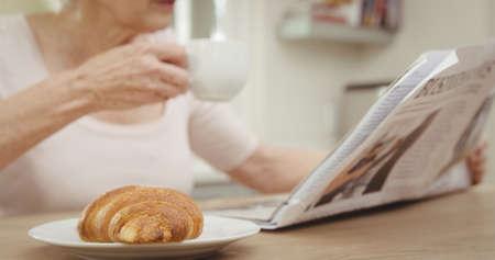 Senior woman drinking coffee while reading newspaper photo