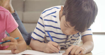 drawing room: Cute siblings drawing on a notebook in the living room