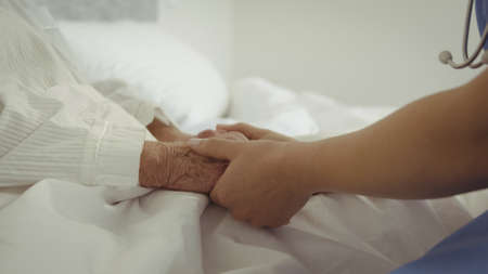 look after: Nurse holding patient hands on bed LANG_EVOIMAGES