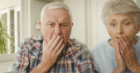 Shocked senior couple looking at home photo