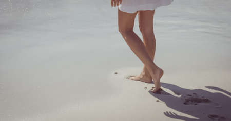 Woman walking on the beach bare footed photo