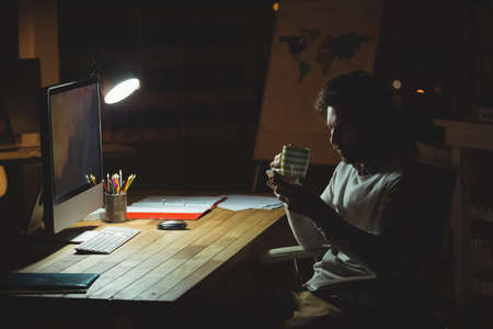 overworking: Businessman using his smartphone at night in the office LANG_EVOIMAGES