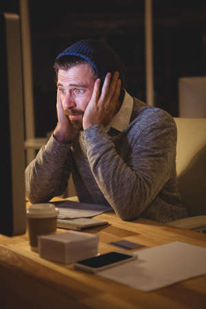 overworking: Hipster looking at computer in the office