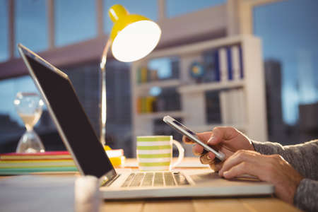 technology: Hands using a smartphone and a laptop by night in office
