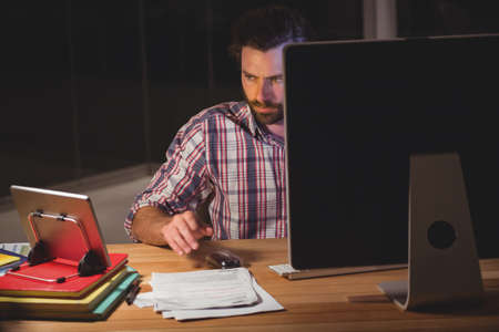 overworking: Hipster using computer and tablet computer in the office