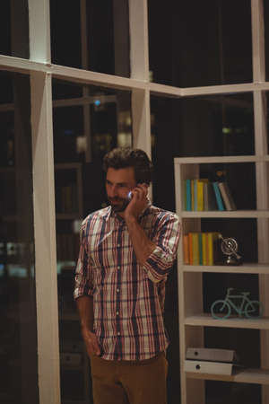 overworking: Hipster calling with his mobile phone in the office