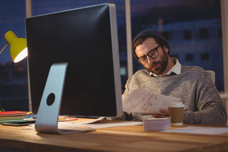 overworking: Hipster reading documents in the office