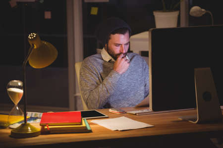 overworking: Hipster using computer in the office