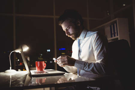 overworking: Businessman using smartphone at night in the office