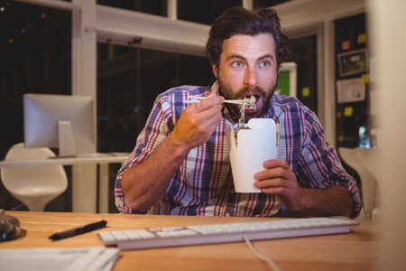 overworking: Hipster eating fast food front of computer in the office