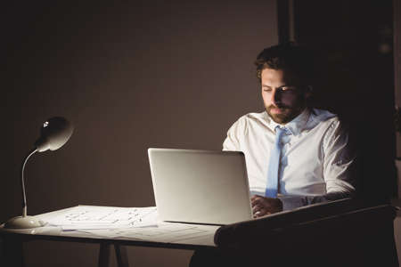 overworking: Businessman using laptop at night in the office