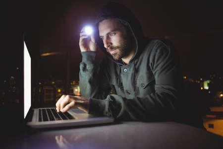 overworking: Hacker using a laptop in dark room