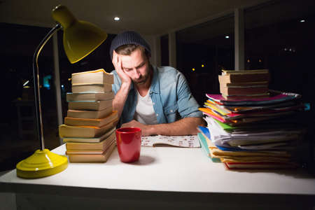 overworking: Thoughtful hipster with stacks of books in the office LANG_EVOIMAGES