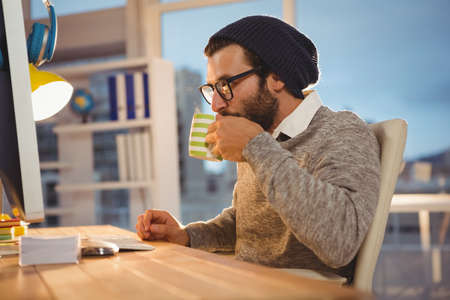 overworking: Hipster drinking coffee front of computer in the office