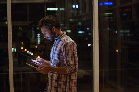 overworking: Hipster holding a smartphone and a tablet computer in the office