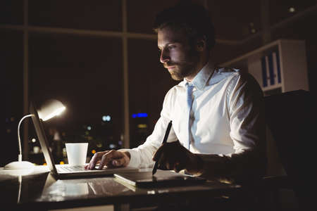 overworking: Businessman drawing on graphic tablet at night in the office