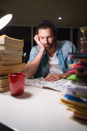 late 20s: Hipster reading a document with stacks of books in the office