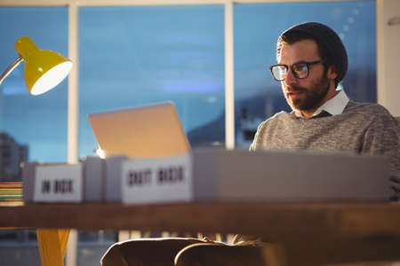 overworking: Hipster using a computer in the office LANG_EVOIMAGES