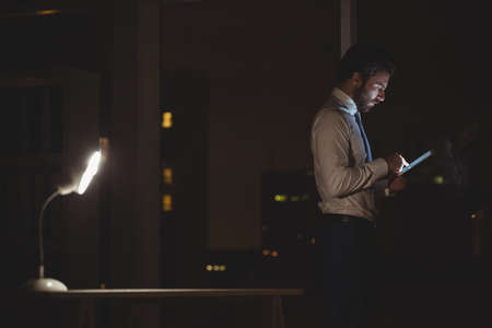 overworking: Businessman using tablet at night in the office