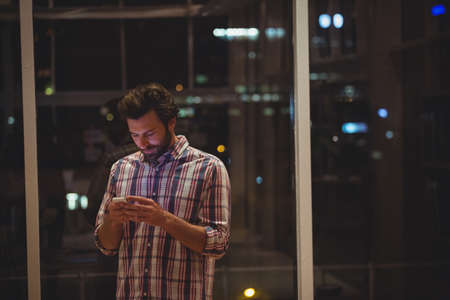 overworking: Hipster using a smartphone in the office
