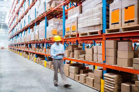 aisle: Warehouse worker walking in an aisle in warehouse