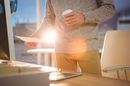overworking: Man reading documents and holding a cup of coffee in the office