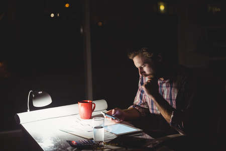 overworking: Hipster using a smartphone in darkness in the office