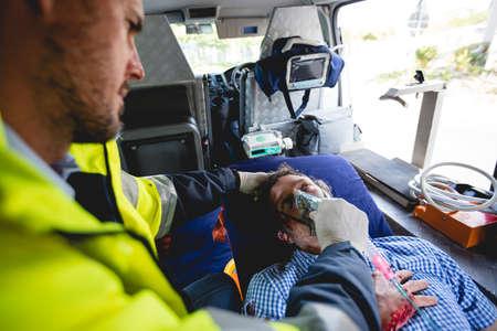hospital trolley: Injured man with ambulance man in ambulance car
