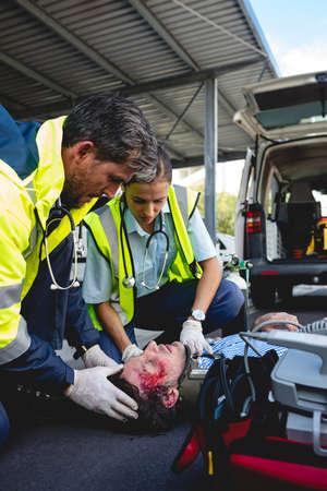 healing practitioners: Ambulancemen healing injured man lying on the ground LANG_EVOIMAGES