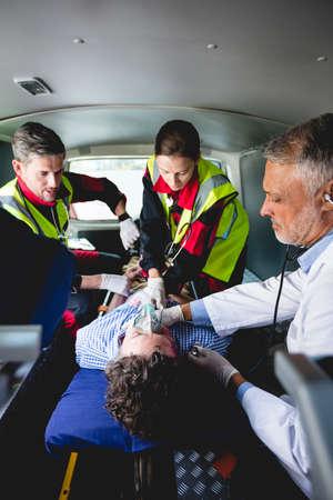hospital trolley: Injured man with ambulance men in ambulance car